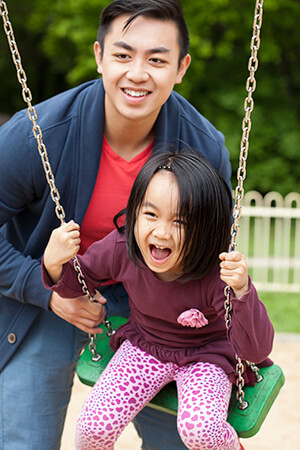 Asian Dad pushes Daughter on Swings