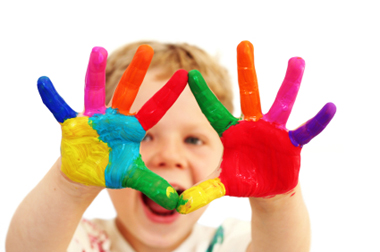 child holding up hands painted in many colors